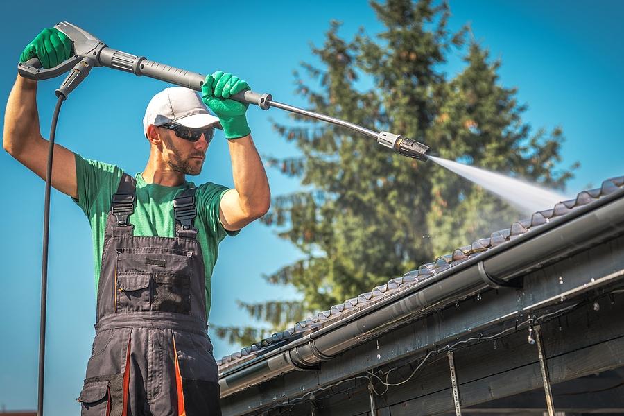 washing plastic transparent carport roof by caucasian men. pressure washer job.